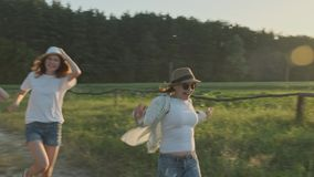 Happy mother and three daughters running along a country road. Summer nature background, golden hour stock video