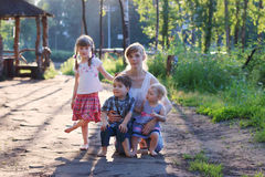 Happy mother with three little barefoot children pose Stock Photos