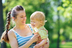 Happy mother tickling baby outside Stock Image