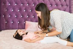 Young Woman Making Little Girl Laugh By Tickling. Happy mother tickling cute girl lying on bed at home royalty free stock images