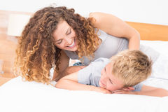 Happy mother tickling her son on bed Stock Images