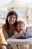 Happy mother and  toddler   with laptop at  beach Royalty Free Stock Image