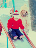 Happy mother with  toddler playing on slide. In winter Royalty Free Stock Photo