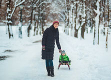 Happy mother with toddler on sled in winter Royalty Free Stock Photo