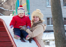 Happy mother with  toddler on slide   in winter. Happy mother with  toddler on slide playground area in winter Stock Photos