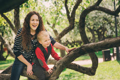 Happy mother and toddler son playing together outdoor and climbing apple tree. In spring or summer Stock Photography