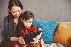 Happy mother and toddler son using tablet at home. Family playing computer or searching internet, electronic devices and kids in modern life stock image
