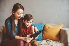 Happy mother and toddler son using tablet at home. Family playing computer or searching internet, electronic devices and kids in modern life stock photos