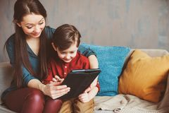 Happy mother and toddler son using tablet at home. Family playing computer or searching internet. Electronic devices and kids in modern life royalty free stock image