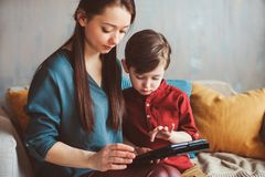Happy mother and toddler son using tablet at home. Family playing computer or searching internet. Electronic devices and kids in modern life royalty free stock photography