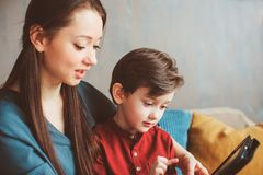 Happy mother and toddler son using tablet at home. Family playing computer or searching internet. Electronic devices and kids in modern life stock photography