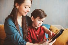 Happy mother and toddler son using tablet at home. Family playing computer or searching internet, electronic devices and kids in modern life royalty free stock photography