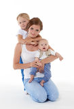 Happy mother with two babies. Young happy mother with sweet  children sit on a white background. Happy family. Six month and four years Royalty Free Stock Image