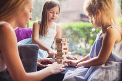 Happy mother with two children playing the wooden blocks tower Stock Photography