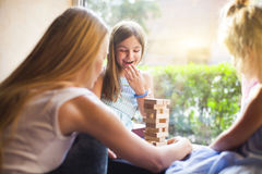 Happy mother with two children playing the wooden blocks tower Royalty Free Stock Photo