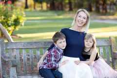 Happy mother with two children sitting on a wooden bench in a garden stock image