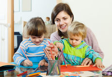 Happy mother and two children sketching on paper Stock Photo