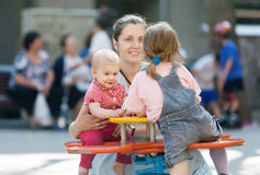 Happy mother with  two children on swing Royalty Free Stock Photos