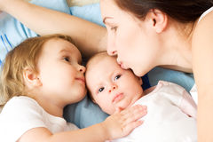 Happy mother with two daughters. Kissing and holding them Royalty Free Stock Photo