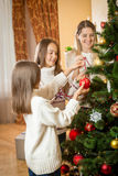 Happy mother and two daughters decorating Christmas tree with ba Royalty Free Stock Photo