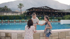 A happy mother with two daughters embraces and enjoy life. In the background there is a swimming pool. stock video footage