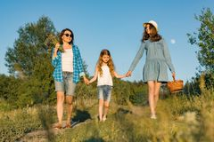 Happy mother and two daughters holding hands walking along rural country road with wildflowers, basket of berries. Sunny summer. Day, sunset stock photo
