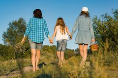 Happy mother and two daughters holding hands walking along rural country road with wildflowers, basket of berries. Sunny summer. Day, sunset, back view stock photography