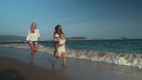 Happy mother with two daughters running along the beach of South China Sea, Yalong Bay slow motion stock footage video. Happy mother with two daughters running stock video footage