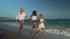 Happy mother with two daughters running along the beach of South China Sea, Yalong Bay slow motion stock footage video. Happy mother with two daughters running stock footage