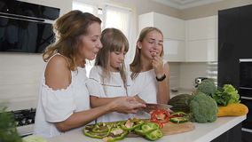 Happy mother and two her daughters is cooking vegetables for dinner at home kitchen. Food, healthy eating, family. The girls dressed in white dresses prepare stock video