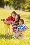 Happy mother with two kids, taking pictures in the park. Outdoor Royalty Free Stock Images