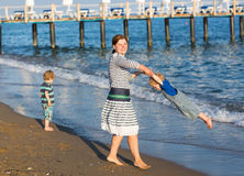 Happy mother and two little children walking on the beach Stock Photos