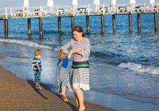 Happy mother and two little children walking on the beach Stock Photography