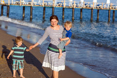 Happy mother and two little children walking on the beach Royalty Free Stock Photography