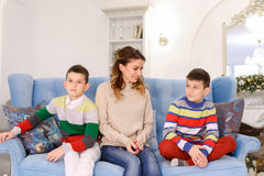 Happy mother of two sons and boys brothers sit side by side and stock photo