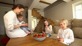 Happy mother with two sons and daughter eating ripe red strawberries. stock video