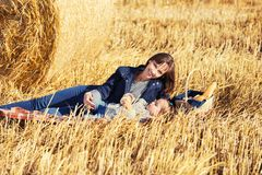 Happy mother and two year old girl next to hay bales in a field. Happy mother and two year old girl next to hay bales in harvested field Royalty Free Stock Photo