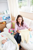 Happy mother unpacking baby clothes at home Stock Photos