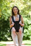 Happy mother walking with infant in baby carrier Royalty Free Stock Image