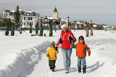 A mother and two children walk on snow track Stock Photography