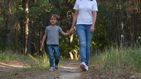 A happy mother walks, holding her son`s hand, talking to him. Mother and child are on a sandy road, walking in the woods stock footage