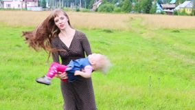 Happy mother whirls little daughter at green meadow stock footage