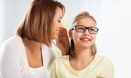 Happy mother whispering secret to daughter at home stock photos