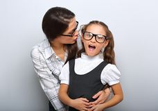 Happy mother whispering the secret to her excite kid in fashion glasses with opened mouth on empty copy space royalty free stock photos