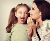 Happy mother whispering the secret to her surprising cute girl i Stock Photo