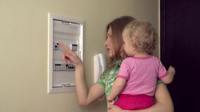 Happy mother woman with little daughter girl turn on lever in fuse box stock footage