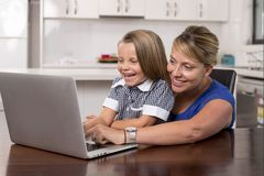 Blond mother woman together with her young beautiful and sweet little girl 6 to 8 years old sitting at home kitchen enjoying with Stock Photo