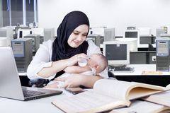 Happy mother working while nursing baby Royalty Free Stock Photos