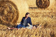 Happy mother and 2 year old girl next to hay bales in harvested. Happy mother and 2 year old girl relaxing next to hay bales in harvested field Stock Images