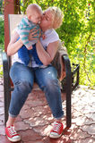 A happy mother 30 years kissing her 4 month old son Stock Images